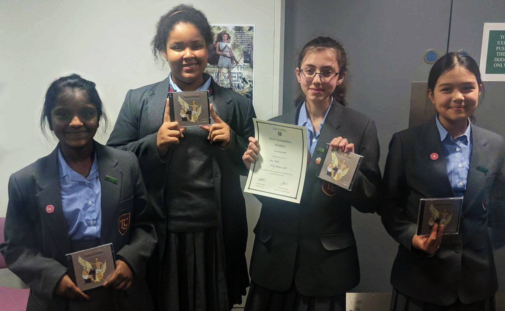 Four students holding certificates and prizes