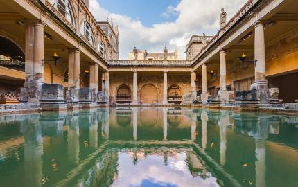 The main bath at Aquae Sulis in the modern day site in Bath, UK. Aspects of the medieval and modern city are reflected in the water.